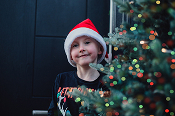 smiling little boy in a santa hat sat at his front door with a twinkling christmas tree