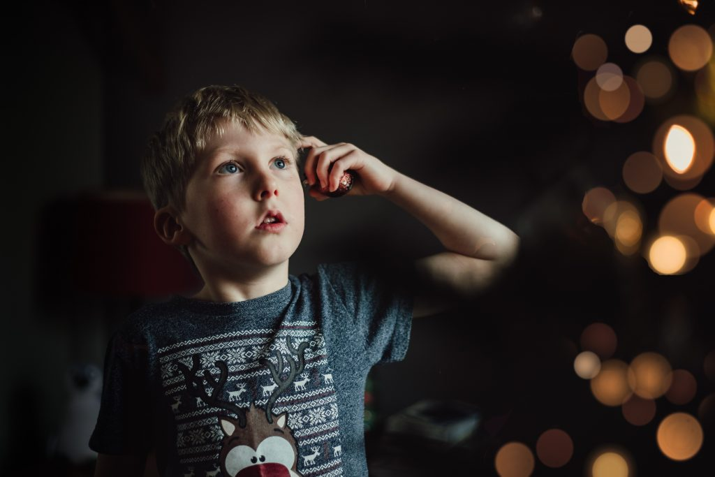 Boy looking up at the christmas tree in wonder