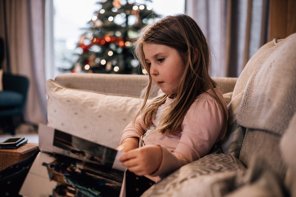 Girl looking at a book on the sofa