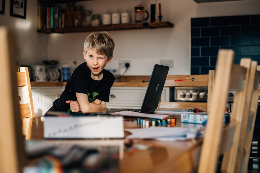 Boy working at the kitchen table and pulling a funny face