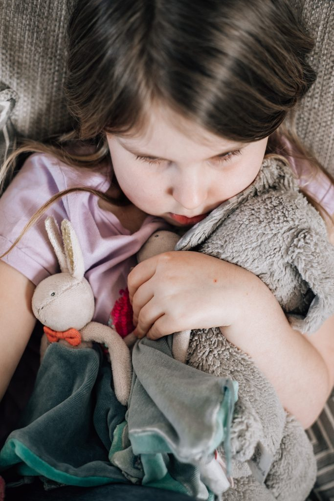 Young girl cuddling her favourite teddies