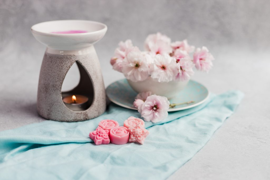 Image of handmade soy wax melts with a burner and flowers on a grey stone backdrop